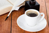 Cup of coffee with a quill pen and inkwell on wooden background — Stock Photo