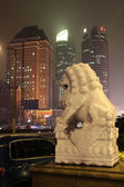 Traditional Stone lion with skyscrapers — Stock Photo