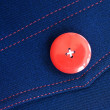 Red button on blue textile — Stock Photo