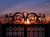 Sunset through iron gate on a cliff — Stock Photo