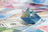 Swiss franc folded as boat on world currencies — Stock Photo