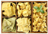 Assorted pasta with fillings in a wooden box — Stock Photo