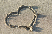 Heart shape on sand beach — Stock Photo