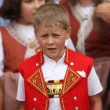 A boy in traditional Swiss costume is  yodeling - Stock Photo