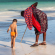 A Massai young man with a little boy on the beach — Stock fotografie