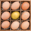 Golden egg among normal eggs in wooden box — Stock Photo #23130864