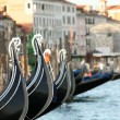 Venetian gondola with Venice city in the blurry background - Stock Photo
