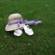 Stock Photo: Lady hat and slippers on meadow