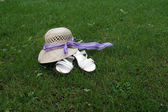 Lady hat and slippers on the meadow — Stock Photo