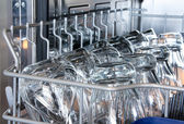 Details of a dishwasher (focus on the front row of glasses) — Stock Photo