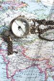 Un reloj antiguo con la superficie de la esfera en un mapa del mundo — Foto de Stock