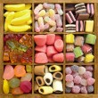 Assorted candy in wooden box — Zdjęcie stockowe #27077287