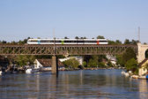 Commuter train crossing the railway on a bridge over the Rhine river — Stock Photo