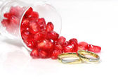 Pomegranate seeds and marriage rings, macro, high-key. — Stock Photo