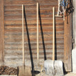 Farm tools in front of a Swiss wooden old barn  — Stock Photo