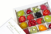 Chocolate box with fresh fruit contents — Stock Photo