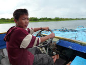 A school boy drives a boat with merely functioning motor — Stock Photo