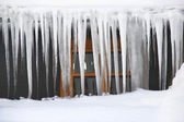 Icicles hanging over the roof in a severe winter — Stock Photo