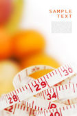 Measuring tape with different fruits at the background — Stock Photo