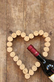 Wine bottle and wine cork on old wooden board — Stock Photo