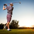 Male golf player teeing off golf ball from tee box to beautiful sunset — Stock Photo
