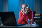 Young bored female college student studying poorly at late evening — Stock Photo