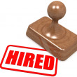 Stock Photo: Hired word on wooden stamp