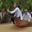Stock Photo: Vietnamese woman rowing a boat in Mekong River in Vietnam