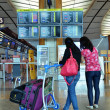 Tourists check the information board in Changi Airport, Singapore — Stock Photo