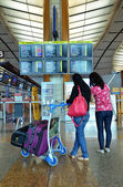 Tourists check the information board in Changi Airport, Singapore — Stockfoto