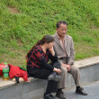 Chinese couple sit on the road side — Stock Photo
