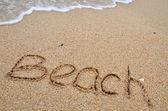 Palabra de playa en la playa de arena — Foto de Stock