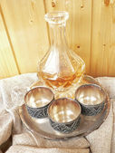 Glass decanter wint three melchior cups isolated on white — Stock Photo