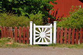 White gate with red fence. — Stock Photo