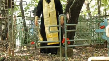 Ruská pravoslavná církev. kněz je modlitební služba na hřbitově. — Stock video