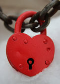 Red closed lock in the form of heart on the background of snow — Stock Photo