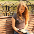 A young girl reading a book on a bench. Summer city park — Stock Video