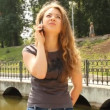Young long-haired woman talking on a mobile phone — Stock Video