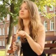 The young girl on a walk in the park drinks water from a bottle — Stock Video