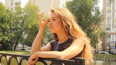 En ung flicka med en cigarett — Stockvideo