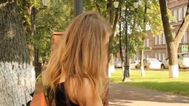 Young girl reading a glossy magazine in the park — Stock Video