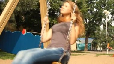 Young girl swinging on a swing in the park — Stock Video