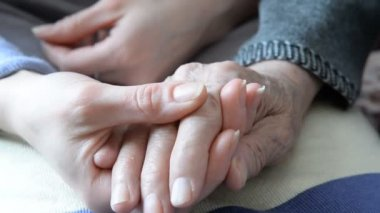 Hand in hand. Hand of an elderly woman in the hand of a young girl — Stockvideo