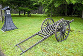 Wooden cart wagon on green field — Stock Photo