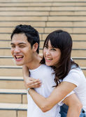 Lovely couple piggy back ride on the stairs2 — Stockfoto