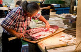 Fish merchant is cutting fish — Stock Photo