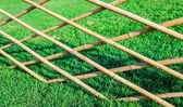 Crossed bamboo fence with green grass in the garden1 — Stock Photo