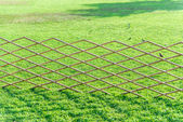 Crossed bamboo fence with green grass in the garden6 — Stock Photo