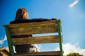 Backside of Woman sit on wooden chair with blue sky2 — Stock Photo
