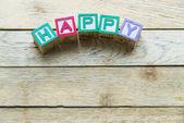Wooden block word is HAPPY on wooden background — Foto de Stock